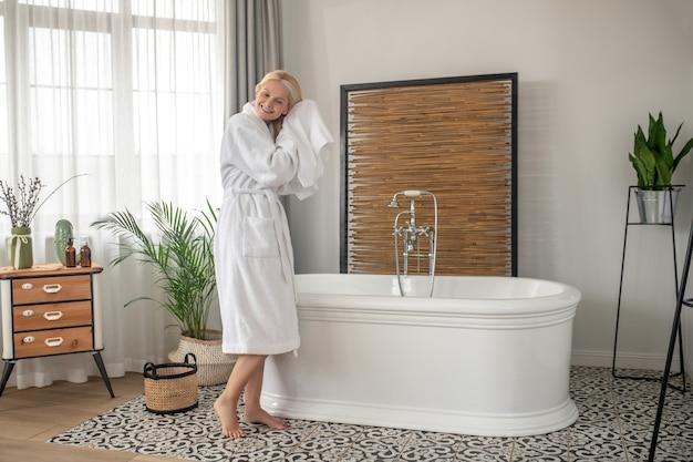 入浴後。入浴後にタオルで髪を乾かす笑顔の金髪女性