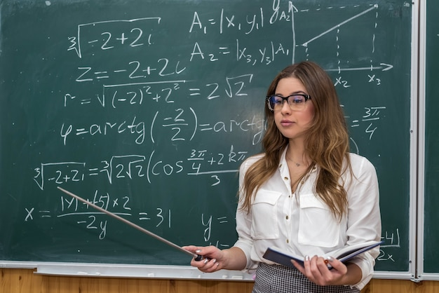 After writing a mathematical equation, the young teacher calls the student to the board so that he can explain everything