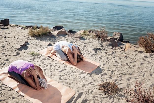 ヨガの後。砂浜でのヨガの時間の後に体を伸ばす健康的なフィットの男性と女性