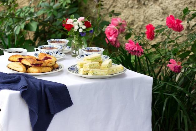 庭でのアフタヌーンティー、スコーン、いちごジャム、フィンガーサンドイッチとキュウリと卵のサラダ。
