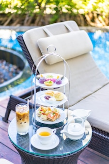 Afternoon tea set with latte coffee and hot tea on table near chair around swimming pool