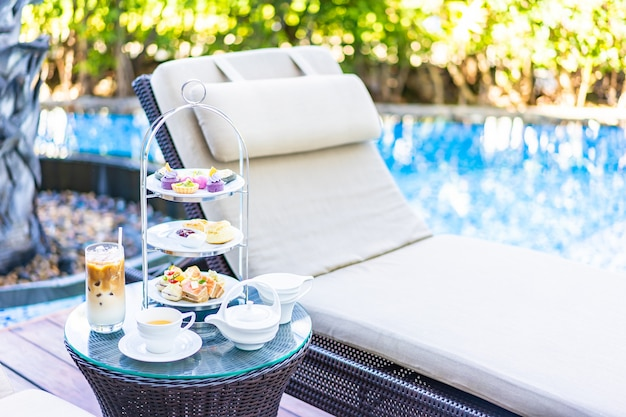 Afternoon tea set with latte coffee and hot tea on table neary chair around swimming pool