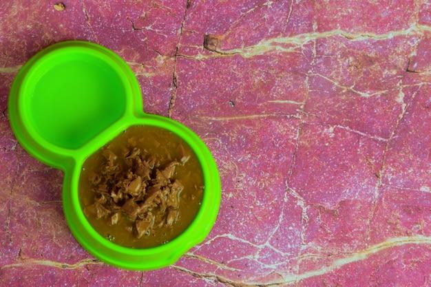 灰色の木の板を背景に、飼料用の乾燥食品で満たされた緑色のプラスチックプレートがあります