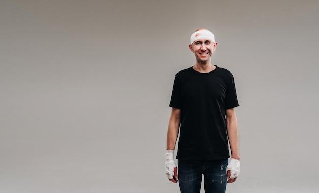 灰色の背景に、黒のtシャツを着たボロボロの男が、頭を包帯で包んで立っています。