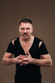 На сером фоне стоит избитый сердитый мужчина в черной футболке с ранами.