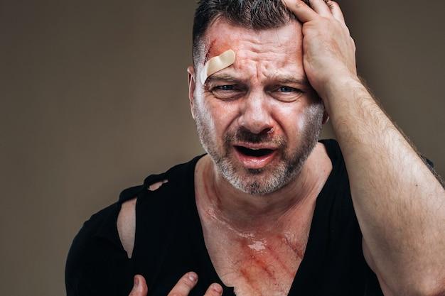 На сером фоне стоит избитый злой мужчина в черной футболке с ранами.
