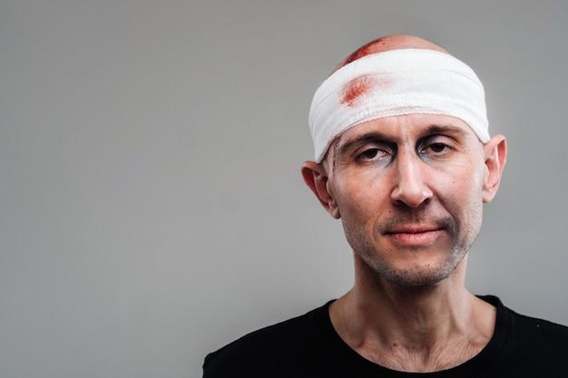 У серой стены избитый и избитый мужчина в черной футболке с перевязанной головой.