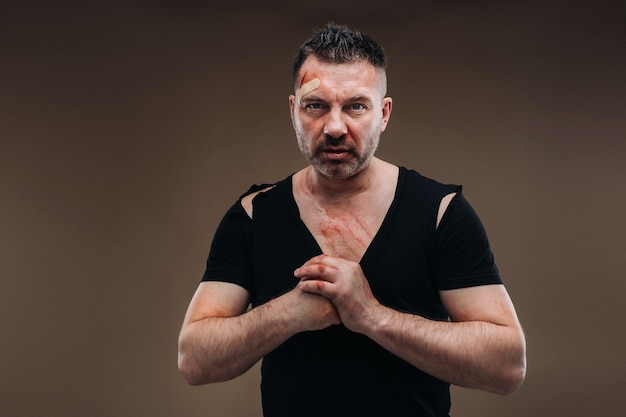 У серой стены стоит избитый сердитый мужчина в черной футболке с ранами.