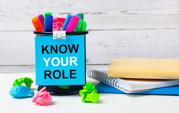 На светлом фоне деревянной стены - стакан с цветными маркерами, смятые яркие листы бумаги и лист синей бумаги с надписью know your role.