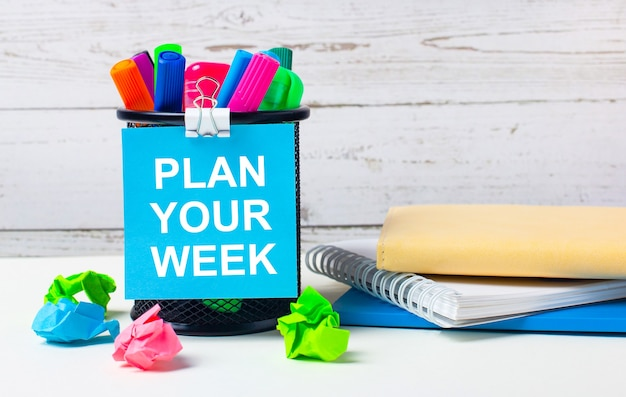 На светлом фоне деревянной стены - стакан с цветными маркерами, смятые яркие листы бумаги и лист синей бумаги с надписью plan your week.