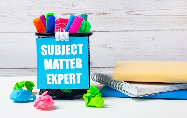 На светлом фоне деревянной стены - стакан с цветными маркерами, смятые яркие листы бумаги и лист синей бумаги с надписью subject matter expert.