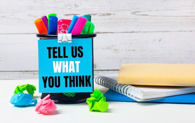 На светлом фоне деревянной стены - стакан с цветными маркерами, смятые яркие листы бумаги и лист синей бумаги с надписью скажи нам, что вы думаете