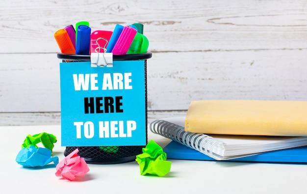 На светлом фоне деревянной стены - стакан с цветными маркерами, смятые яркие листы бумаги и лист синей бумаги с надписью we are here to help.