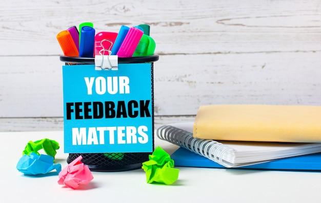 На светлом фоне деревянной стены - стакан с цветными маркерами, смятые яркие листы бумаги и лист синей бумаги с надписью your feedback matters.