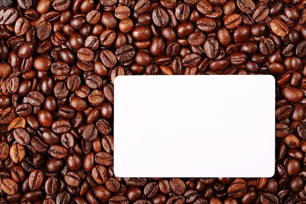 Against the backdrop of coffee beans is a business card