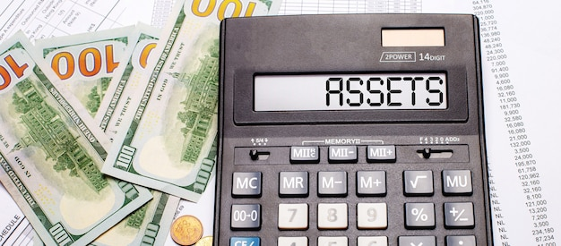 Against the background of cash and documents is a black calculator with the text assets on the scoreboard. business concept