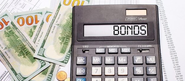 Against the background of cash and documents is a black calculator with the text bonds on the scoreboard. business concept