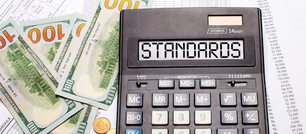 Against the background of cash and documents is a black calculator with the text standards on the scoreboard. business concept