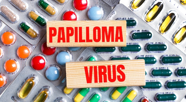 Against the background of multi-colored plates, wooden blocks with the text papilloma virus. medical concept.
