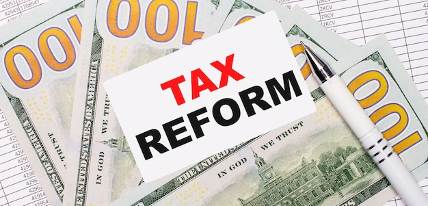 Against the background of reports and dollars - a white pen and a card with the text tax reform. business concept