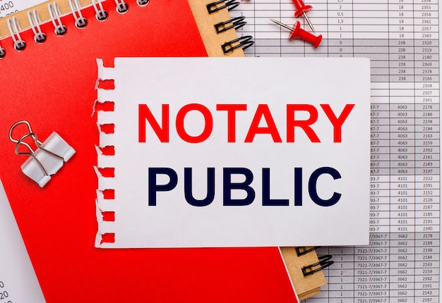 Against the background of the reports, there are red and brown notepads, a white paper clip, red buttons and a white sheet of paper with the text notary public. business concept