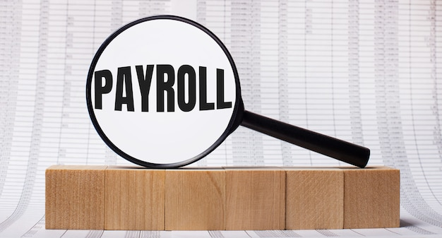 Against the background of reports on wooden cubes - a magnifying glass with the text payroll. business concept