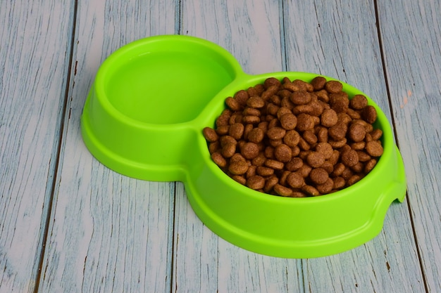 Against the background of wooden boards lies a green plastic plate filled with dry food for feeding cats or dogs and water.