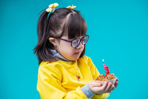青い壁に対して。中に火のともったろうそくとお祝いのカップケーキを探している前髪のかわいい若い女の子
