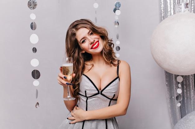 巨大なサイズの明るいクリスマスボールに対して、スパークリングワインのグラスを持った非常に美しい女性がポーズをとる
