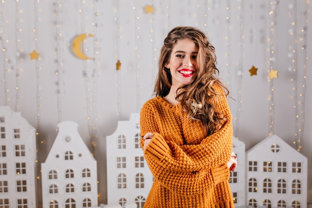 花輪と白い家の形で段ボールの暖かい装飾に対して、美しく、暖かいセーターのポーズで美しい茶色の髪の女性