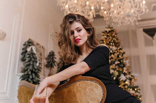 Against christmas decorated tree beautiful long-haired woman with beautiful figure mysteriously looks