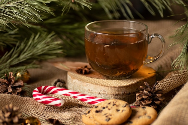 Against the fabric, jgut burlap and branches of a christmas tree stands on a tree tea with cookies and lollipop with cones. evening snack. treats for santa