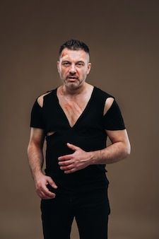 Against a gray background stands a battered angry man in a black t-shirt with wounds