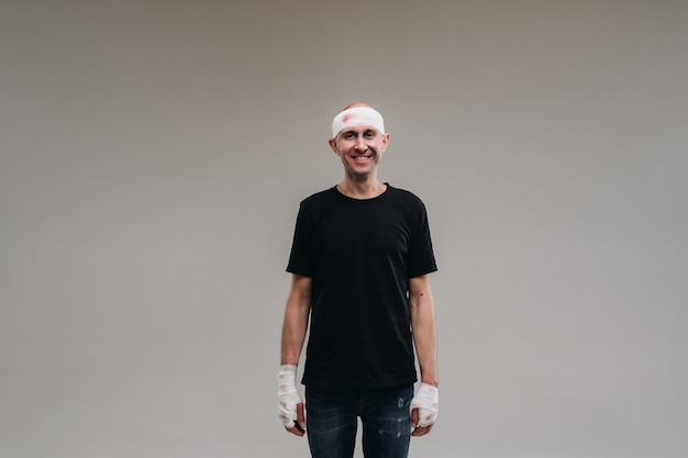 Against a gray background stands a battered and battered man in a black t-shirt with his head wrapped in a bandage.