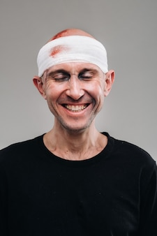Against a gray background stands a battered and battered man in a black t-shirt with his head wrapped in a bandage