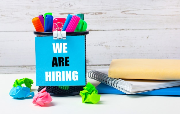 Against a light background of a wooden wall, there is a glass with colored markers, crumpled bright sheets of paper and a sheet of blue paper with the inscription we are hiring