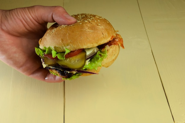 베이지색 나무 테이블을 배경으로 손에는 고기, 치즈, 토마토, 양파, 오이, 샐러드가 포함된 샌드위치가 있습니다.