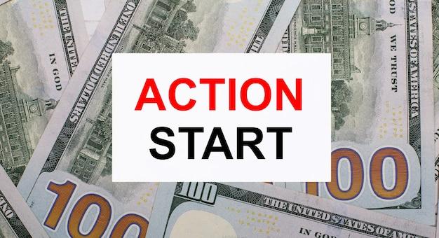 На фоне американских долларов белая карточка с надписью action start. финансовая концепция