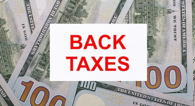 На фоне американских долларов белая карточка с надписью back taxes. финансовая концепция