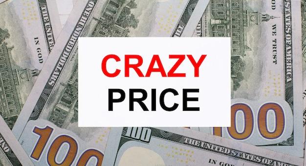 На фоне американских долларов - белая карточка с надписью crazy price. финансовая концепция