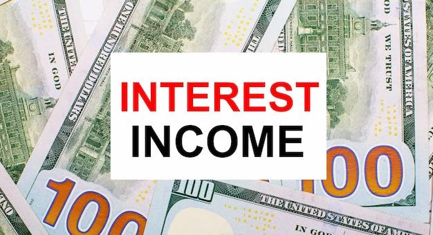 米ドルを背景に、interestincomeというテキストの白いカード。財務コンセプト
