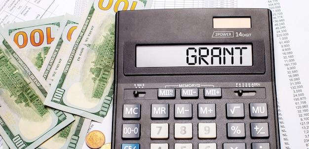 На фоне кассы и документов - черный калькулятор с надписью grant на табло. бизнес-концепция