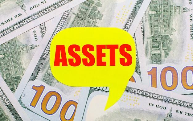 테이블에 흩어져 있는 달러의 배경에는 assets라는 텍스트가 있는 노란색 곱슬 카드가 있습니다. 금융 개념