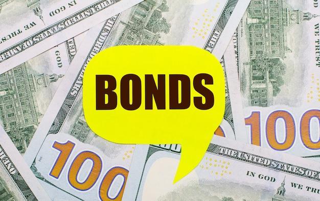На фоне разбросанных по столу долларов - желтая фигурная карточка с текстом облигации. финансовая концепция