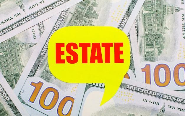На фоне разбросанных по столу долларов - желтая фигурная карточка с надписью estate. финансовая концепция