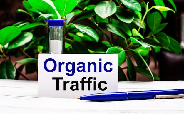 На фоне зеленых листьев растения на столе ручка, песочные часы и карточка с надписью organic traffic.