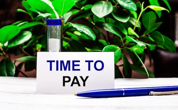 植物の緑の葉を背景に、テーブルの上にペン、砂時計、支払い時間の刻印が書かれたカードがあります。