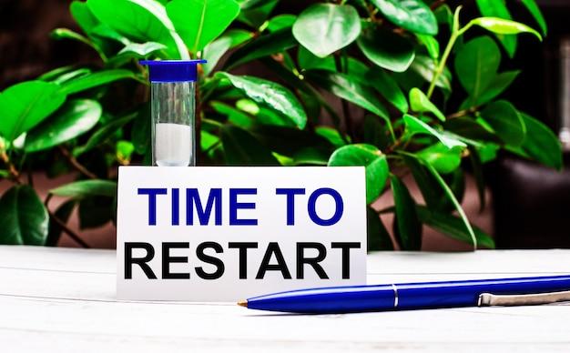 植物の緑の葉を背景に、テーブルの上にペン、砂時計、そして「再開する時間」と書かれたカードがあります。
