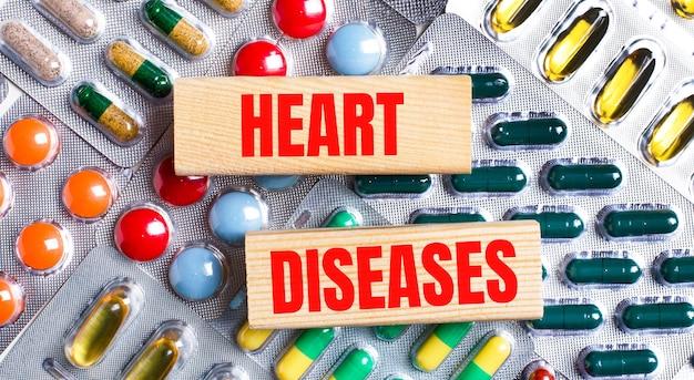 다색 접시의 배경에 심장병이라는 텍스트가 있는 나무 블록. 의료 개념입니다.