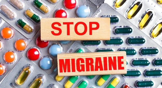На фоне разноцветных табличек деревянные блоки с надписью «стоп мигрени». медицинская концепция.